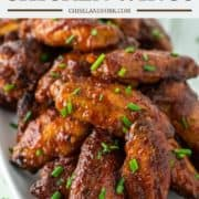 stacked honey bbq wings on white plate with chives