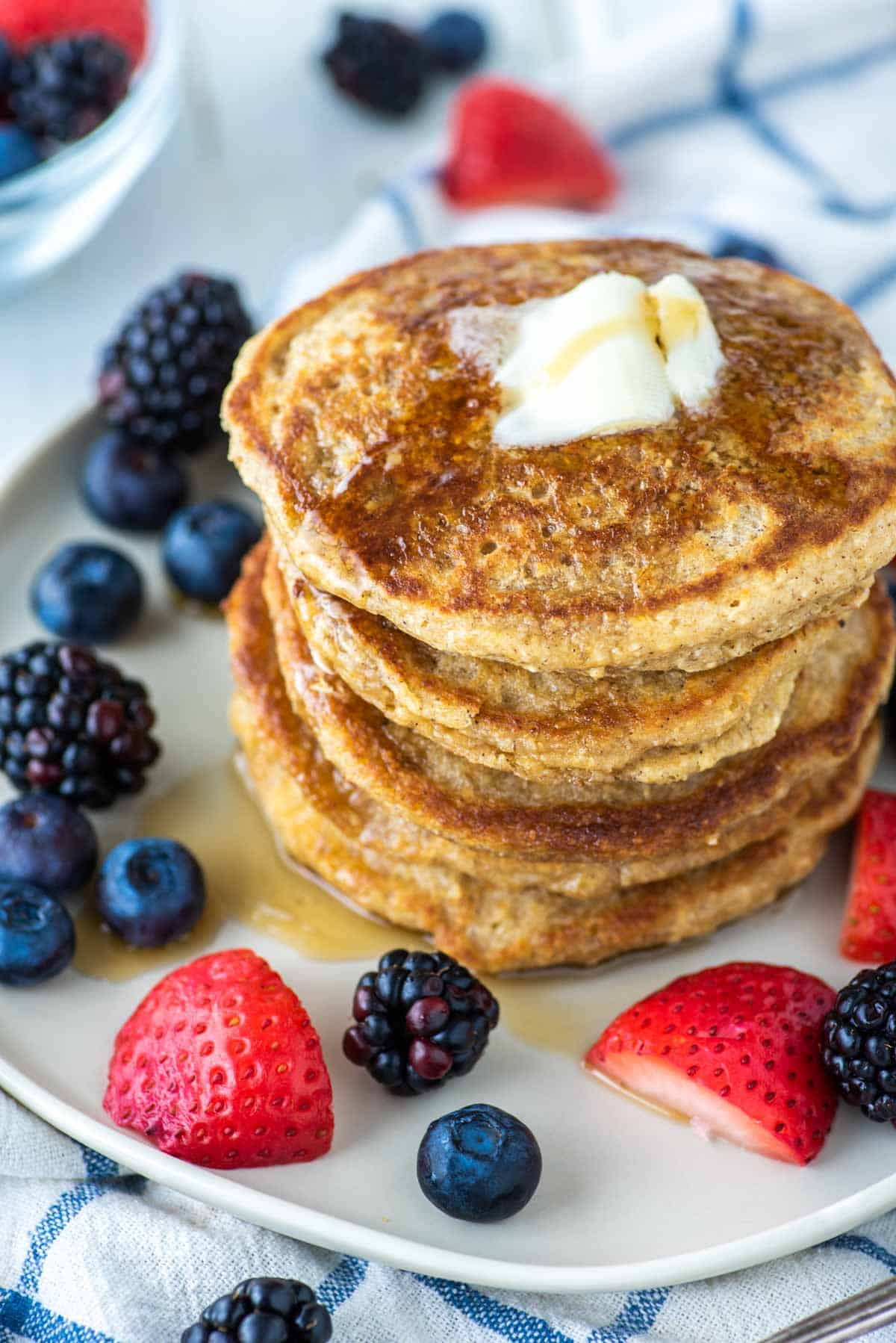 stacked pancakes with butter and fruit on plate