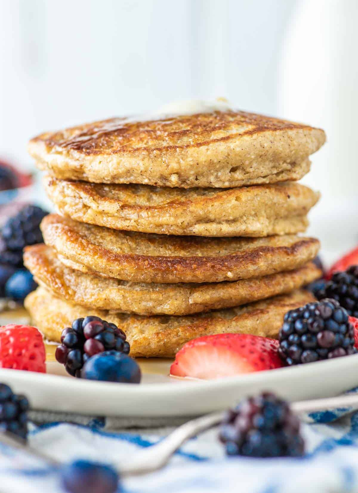 5 stacked oat flour pancakes on plate with fruit