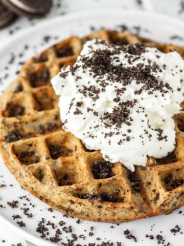 Oreo waffle with whipped cream on white plate