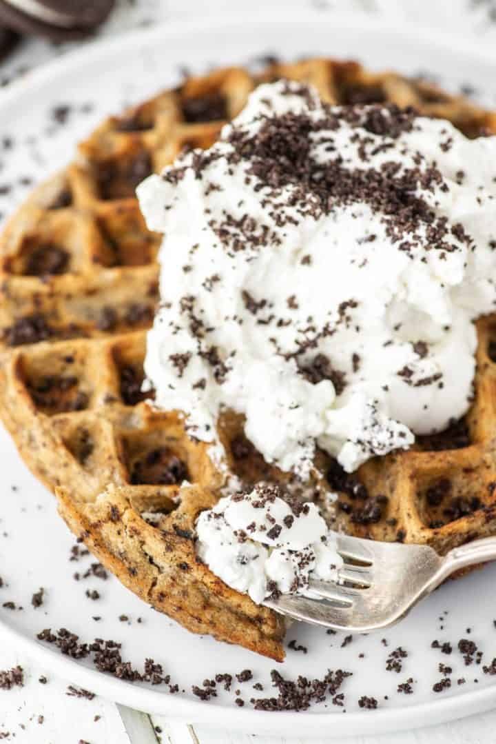fork cut into oreo waffle on white plate with whipped cream