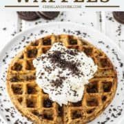 white plate with waffle and whipped cream on top