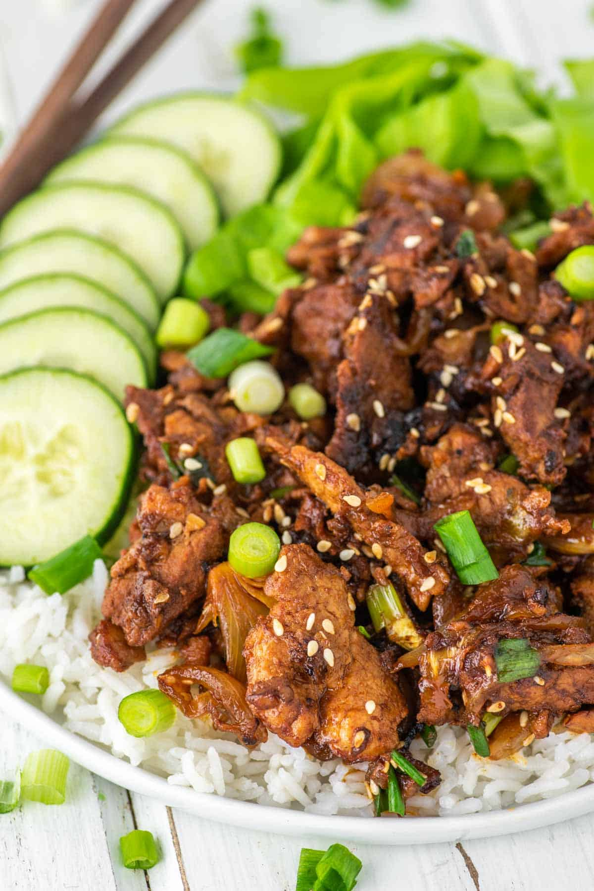 spicy pork bulgogi on white plate of rice with cucumbers and lettuce