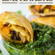 vegetarian empanada cut in half and dipped in chimichurri sauce