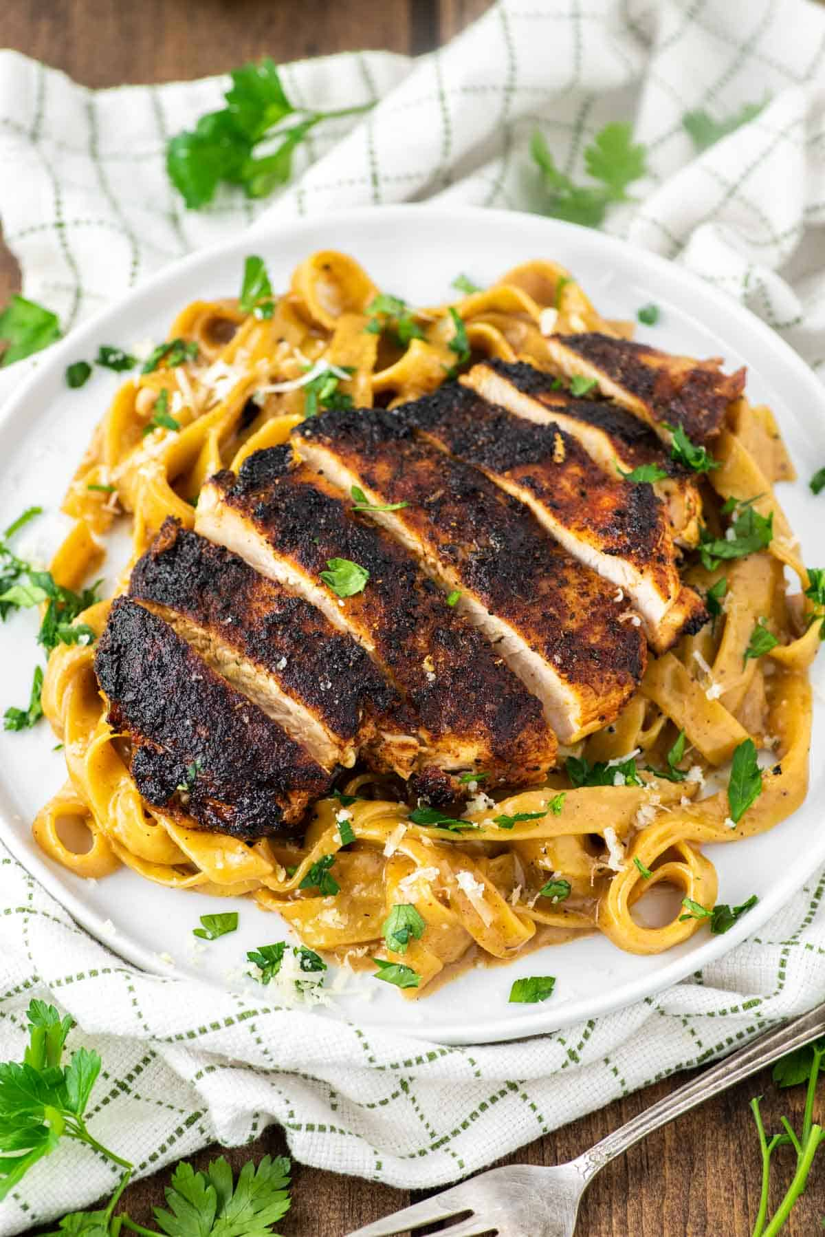 blackened chicken on top of pasta on white dish