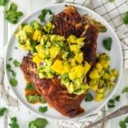 overhead shot of blackened halibut on plate with avocado mango salsa