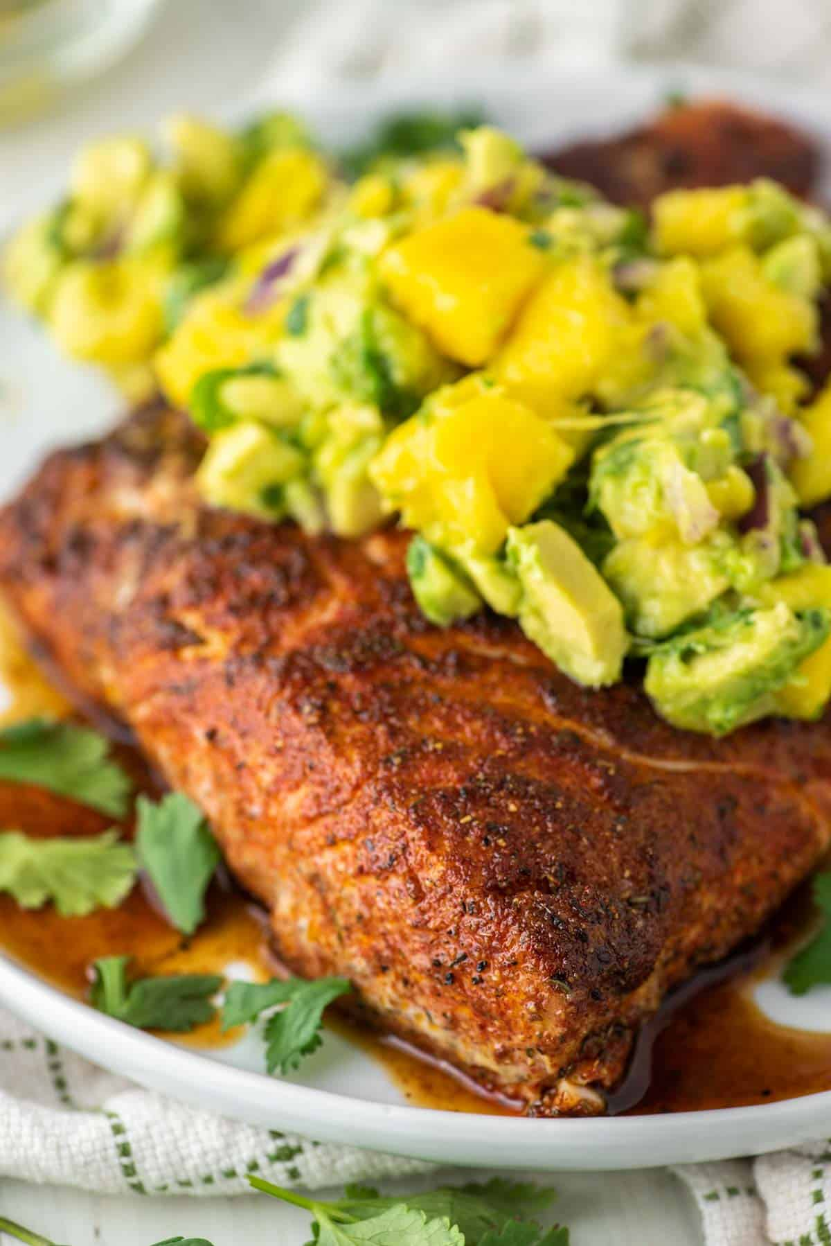 halibut topped with avocado mango salsa on plate