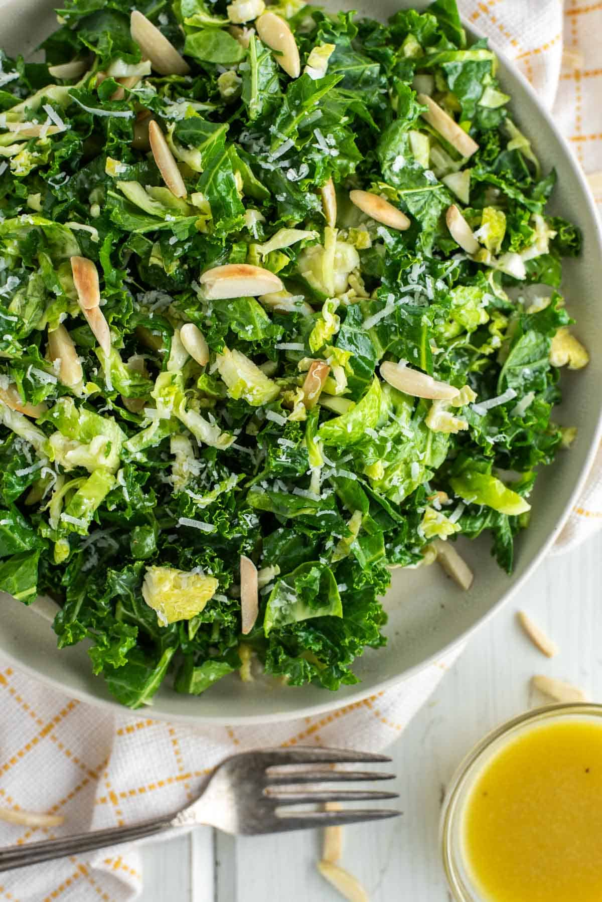 overhead shot of kale crunch salad on plate with fork to the side and bowl of vinaigrette