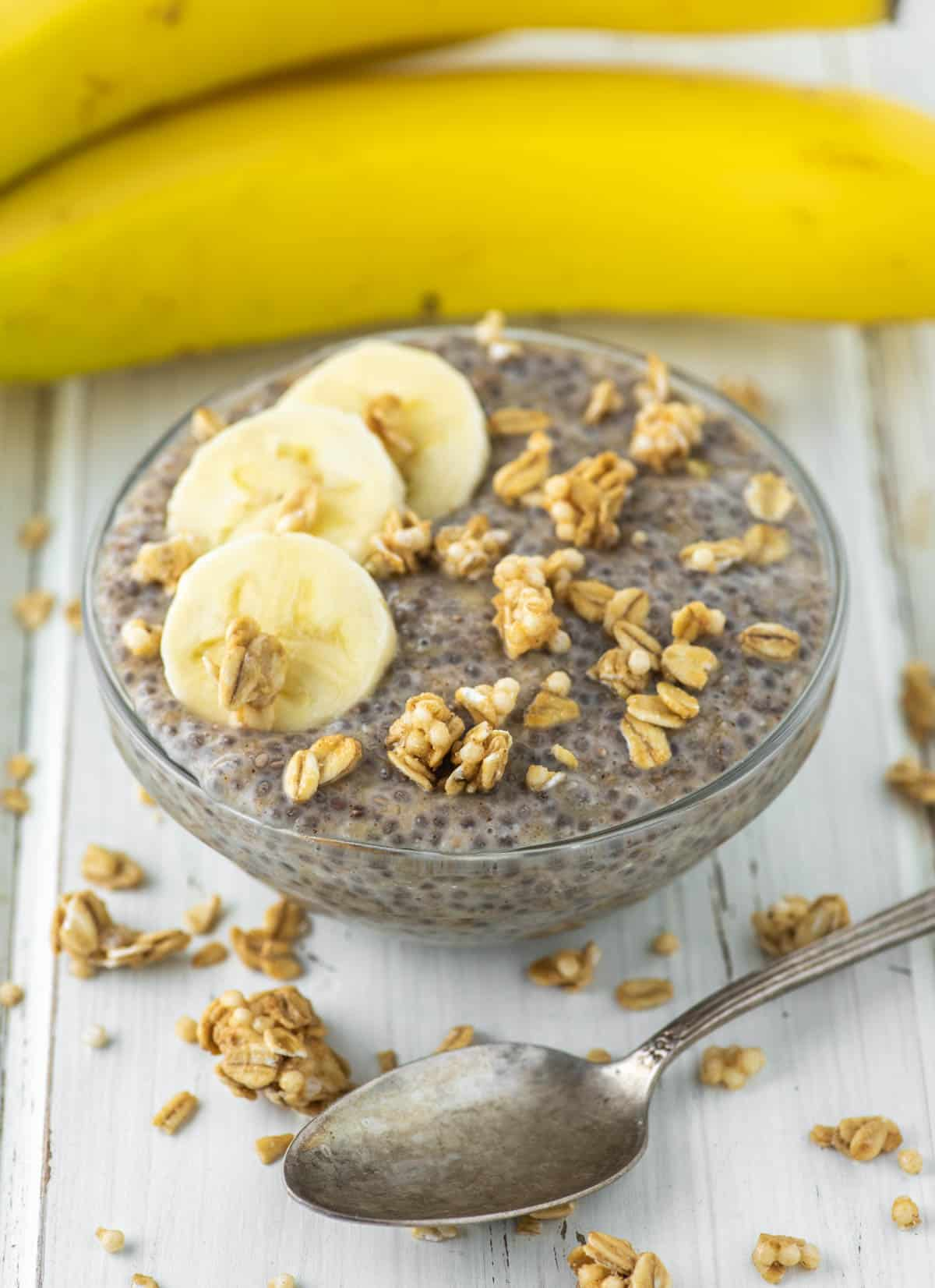 banana chia pudding in glass bowl with bananas in background