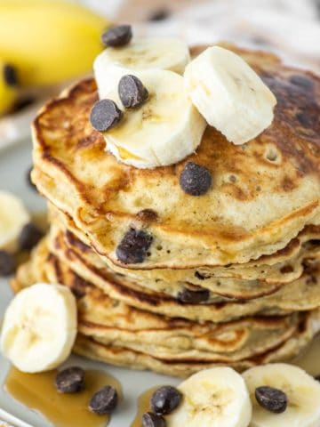banana chocolate chip pancakes stacked on plate with bananas on top