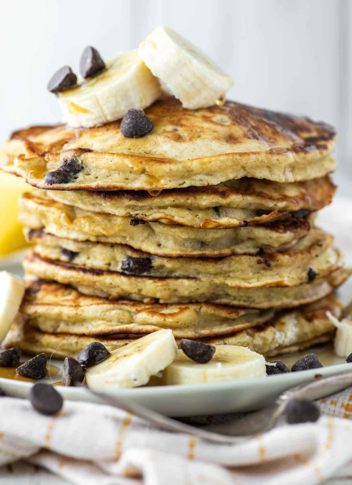 stacked pancakes with bananas and chocolate chips on plate