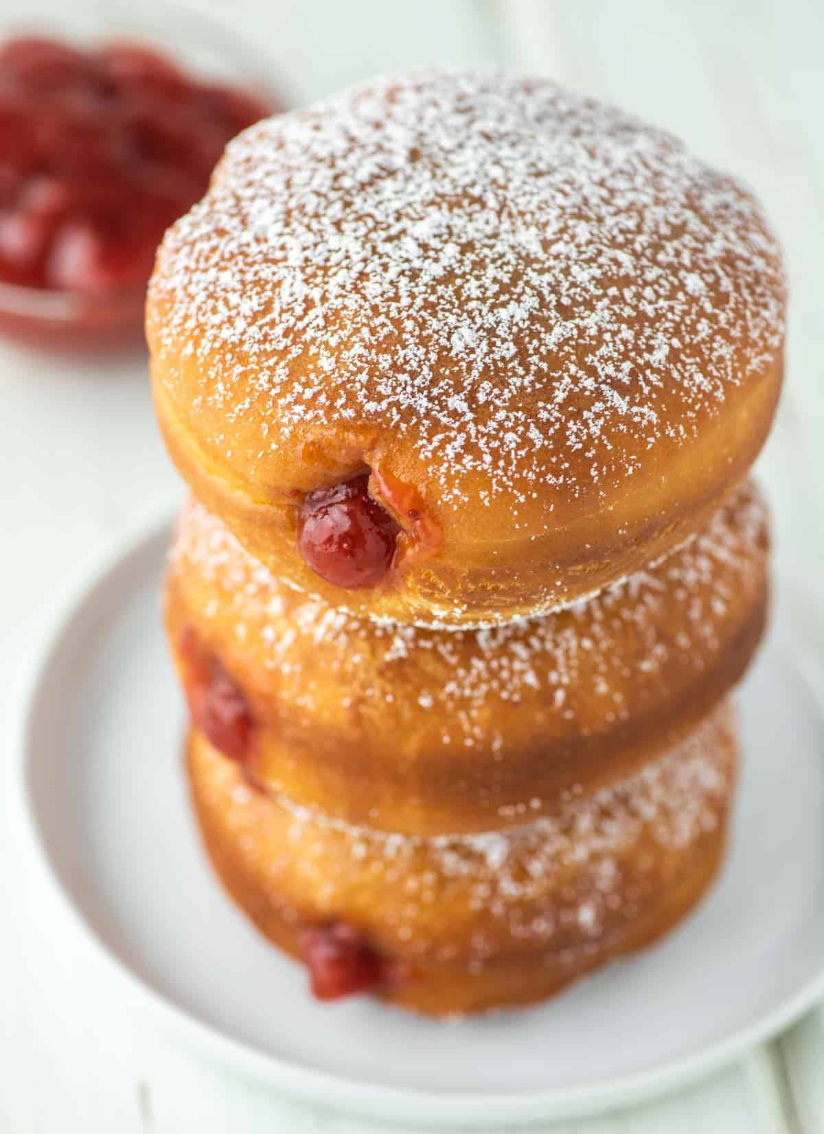 donuts filled with jam stacked on a plate