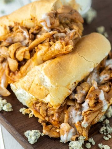 buffalo chicken cheesesteak cut in half and stacked on top of each on wood board