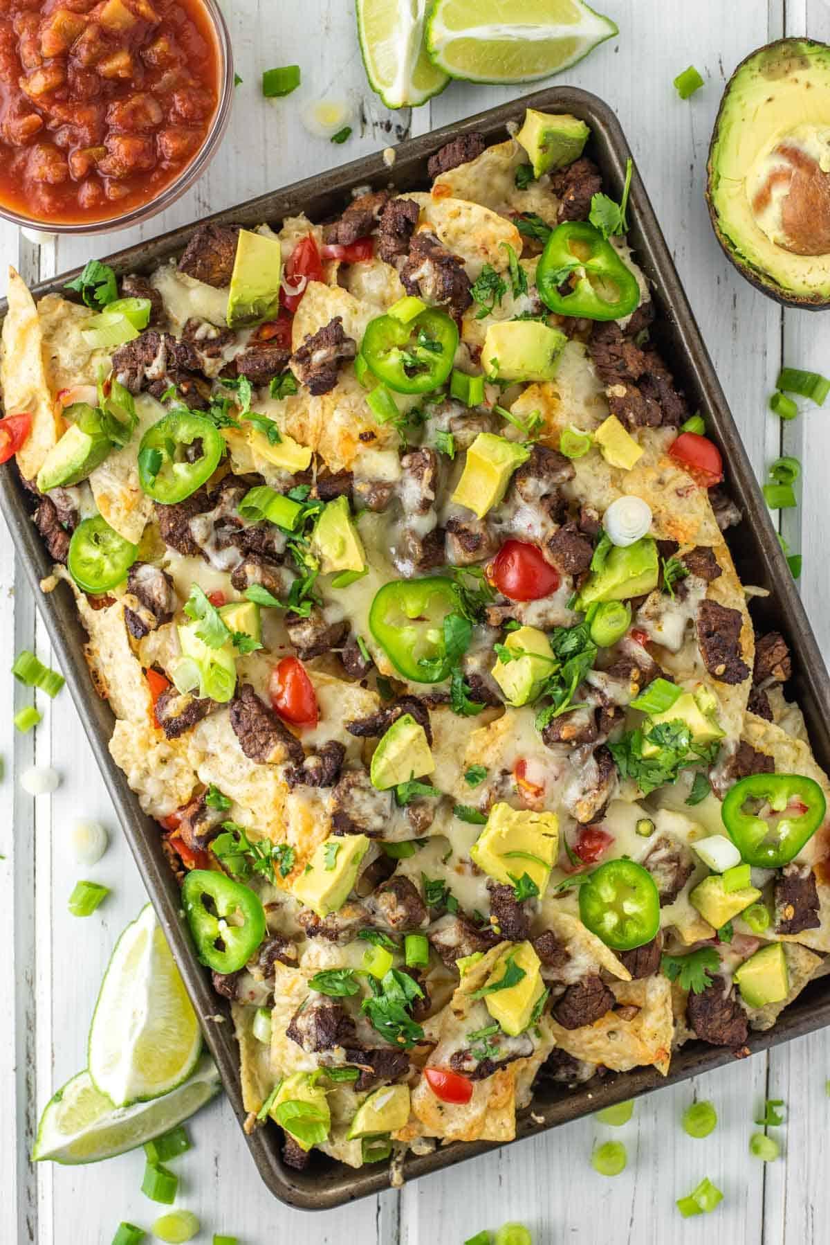 overhead shot of carne asada nachos on baking sheet