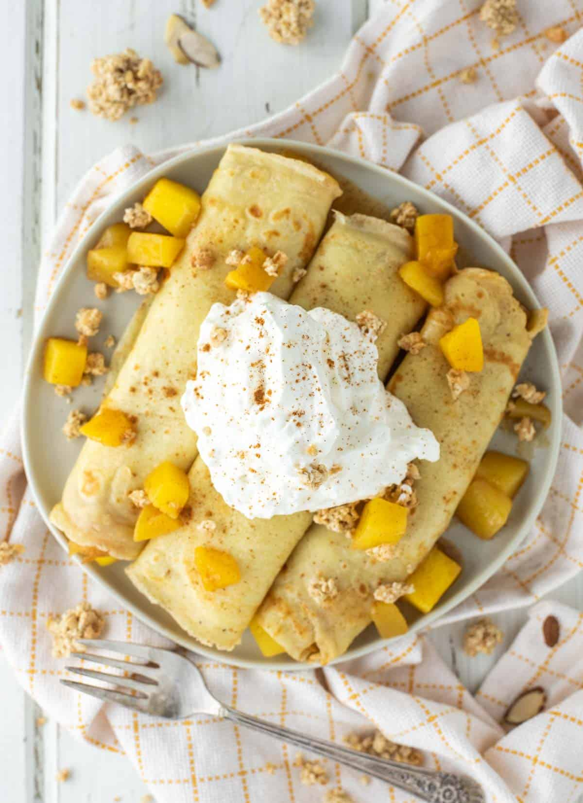 overhead shot of mango crepes on plate with whipped cream on top