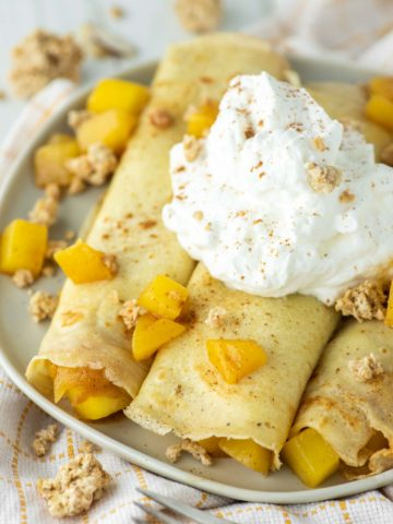 3 mango crepes rolled up on plate with whipped cream on top