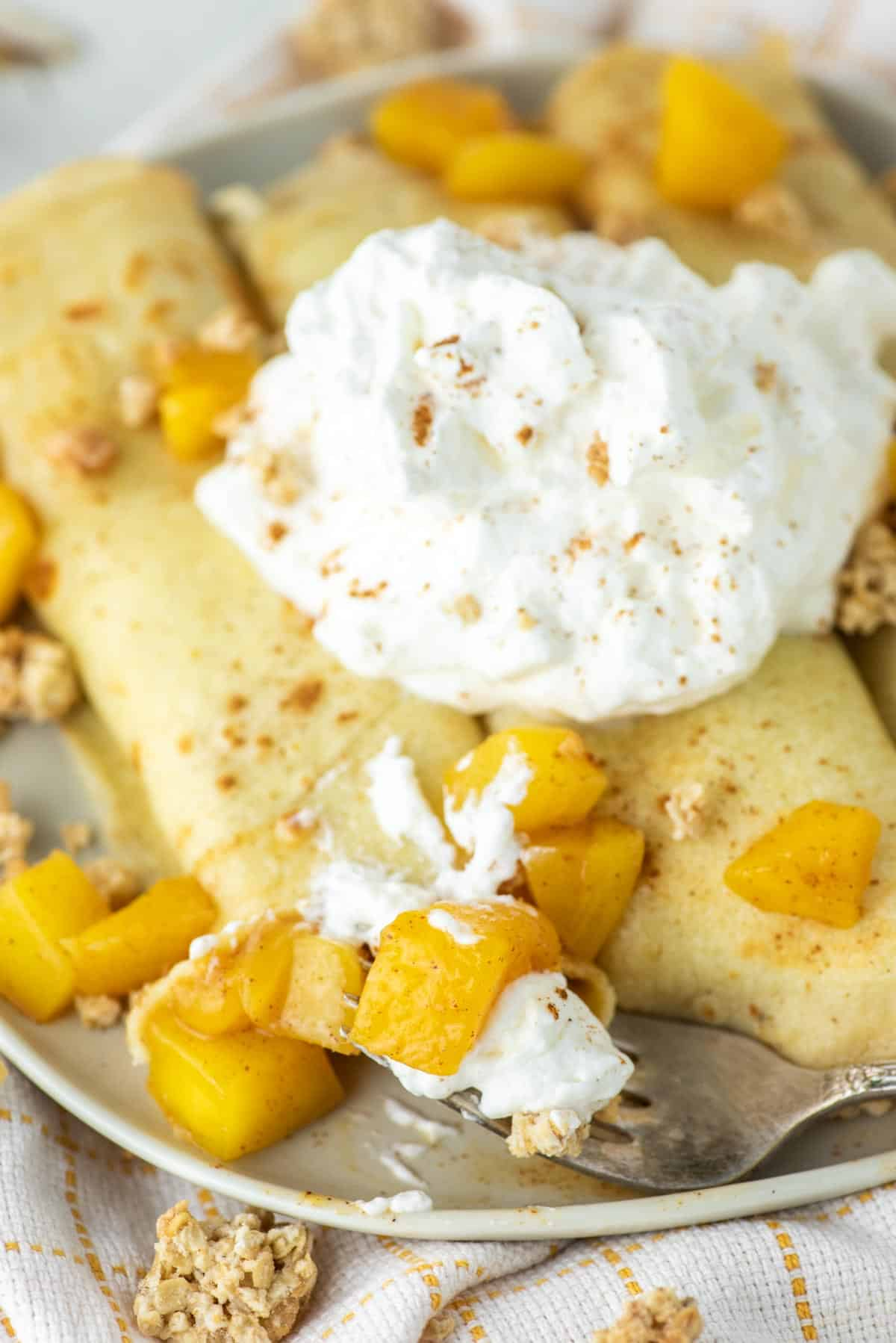 fork taking bite of crepes with mango inside