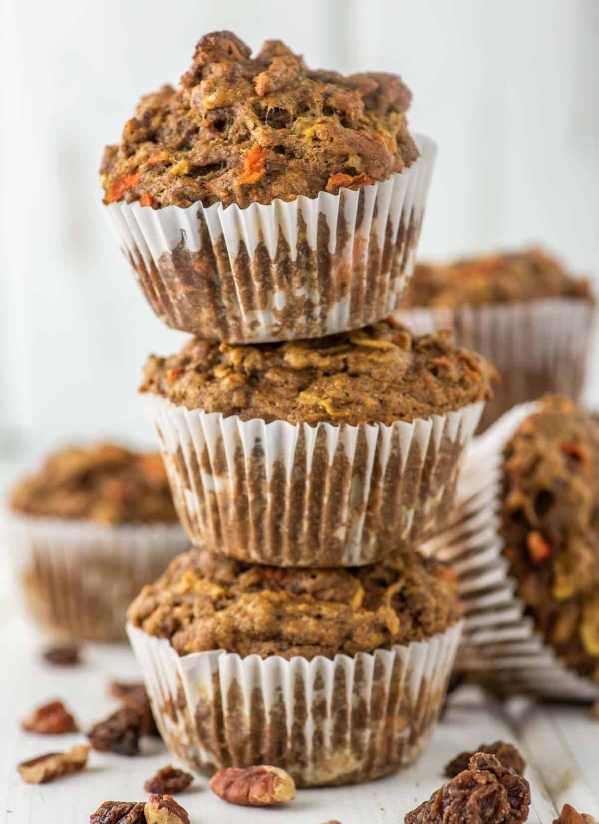 3 stacked morning glory muffins with more in background