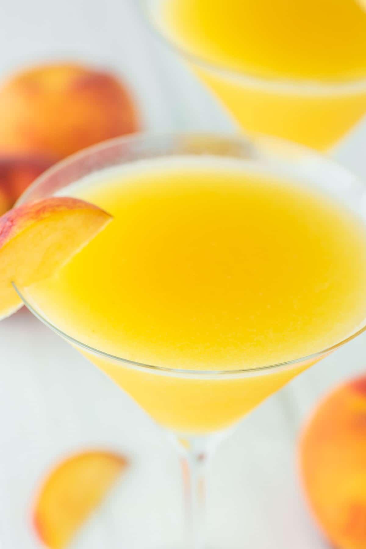 glass of peach martini with slice of peach