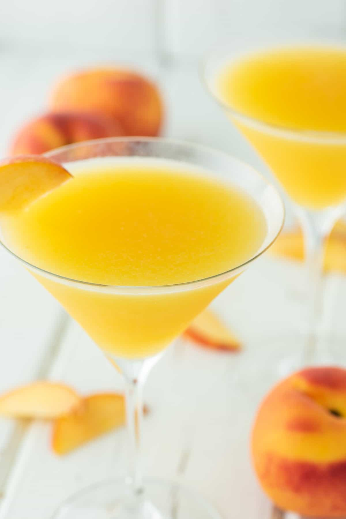 two glasses of martinis with fresh peaches