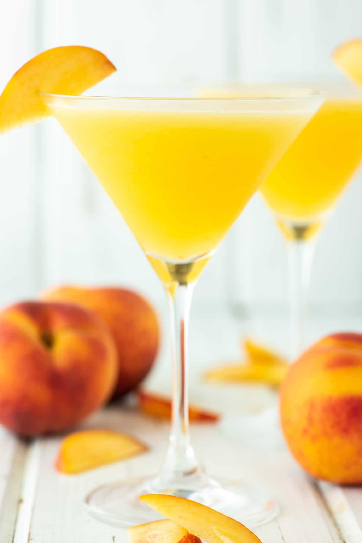 two glasses of peach martinis with fresh peaches on board