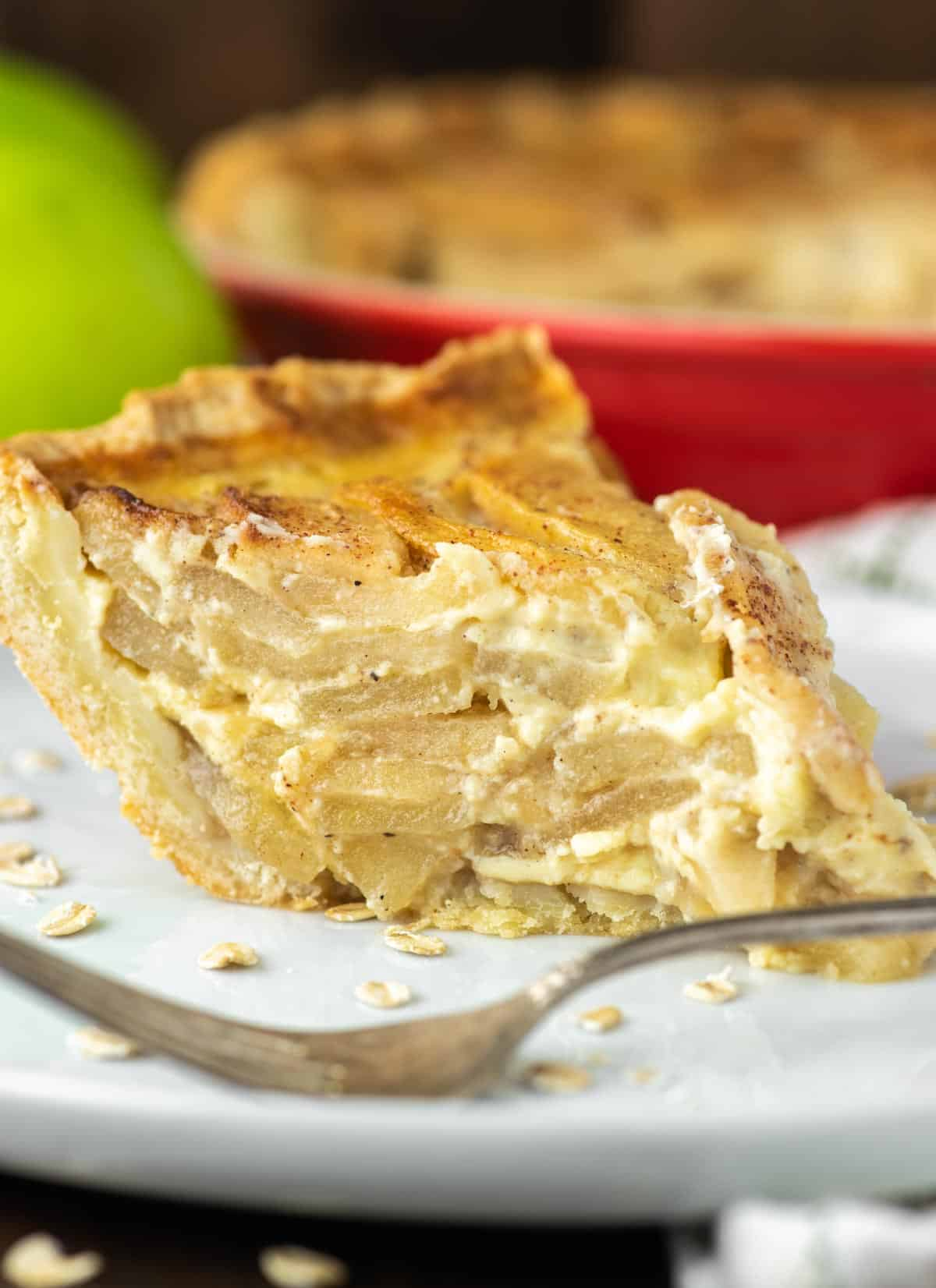 slice of apple custard pie on white plate with fork