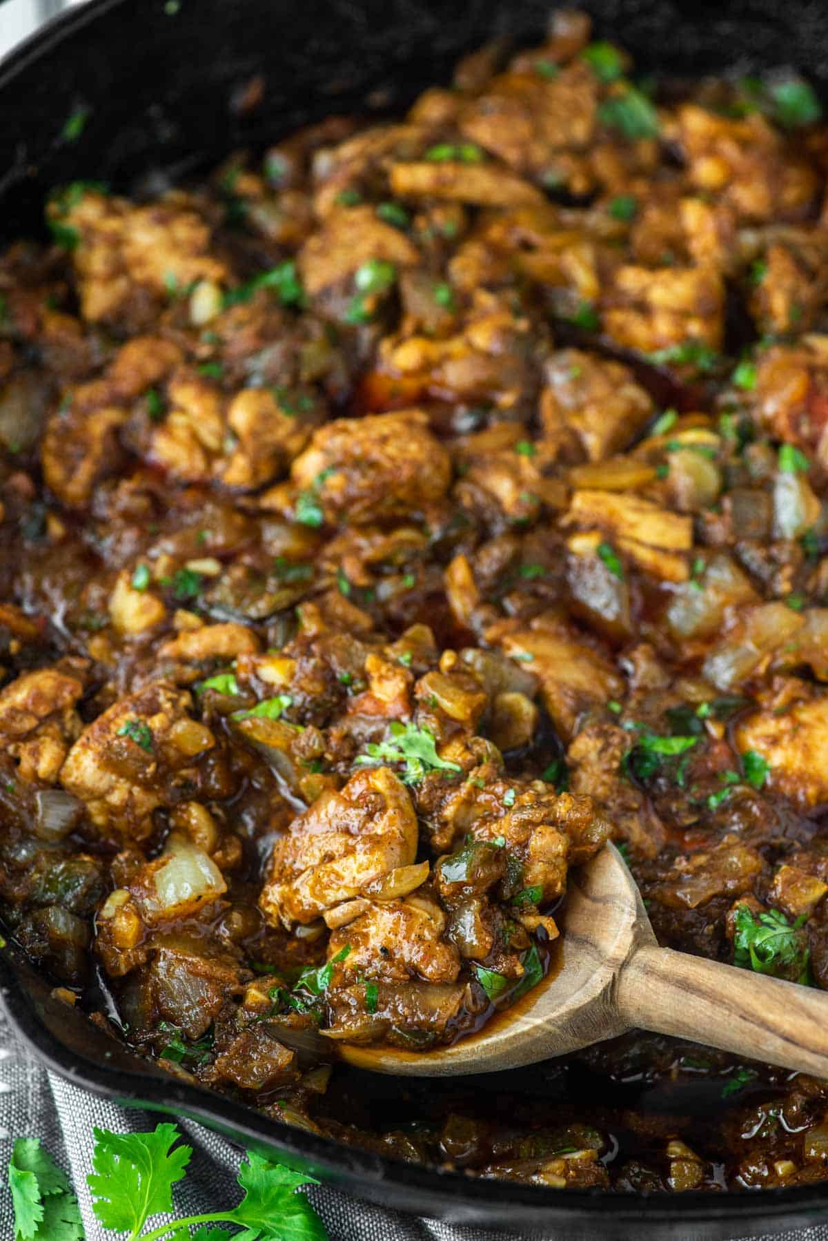wooden spoon dipped in skillet with chicken bhuna