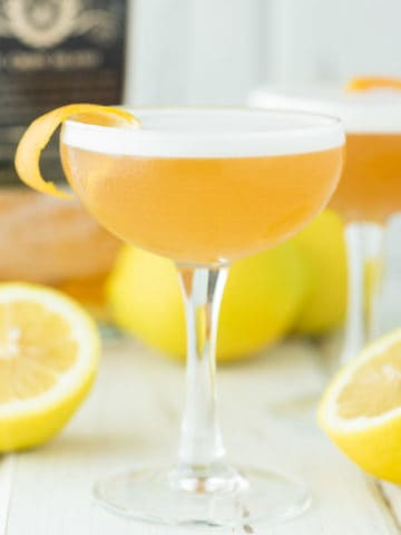 two glasses of rum sours with lemons and dark rum in background