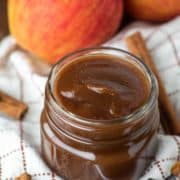 apple butter in glass jar on dish towel
