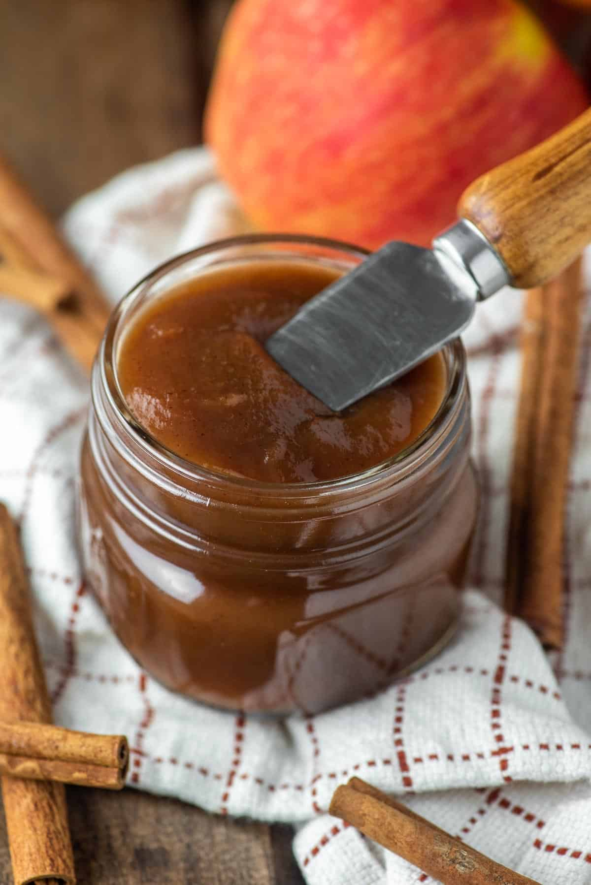 knife dipped in jar of apple butter