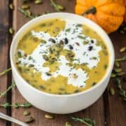pumpkin sweet potato soup in cream bowl with pumpkins in background