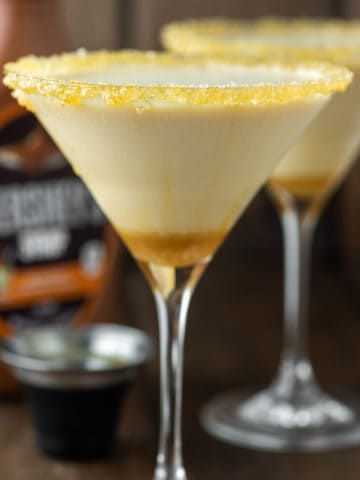 glass of salted caramel martini with another glass and caramel syrup in the background